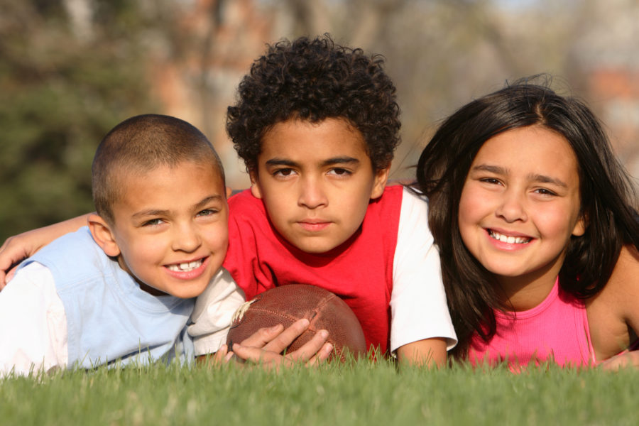 Portrait of multiracial group of kids lying on the grass